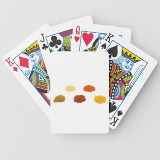 Heaps of several seasoning spices on white bicycle playing cards