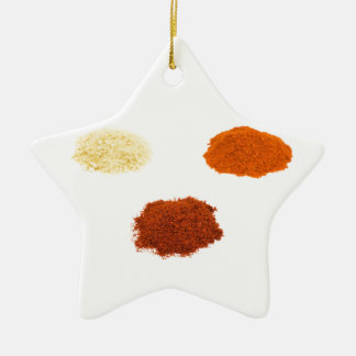Heaps of several seasoning spices on white ceramic star ornament