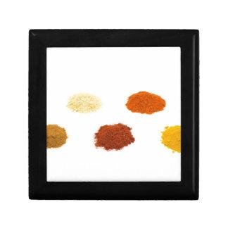 Heaps of several seasoning spices on white keepsake box
