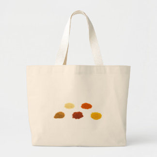 Heaps of several seasoning spices on white large tote bag