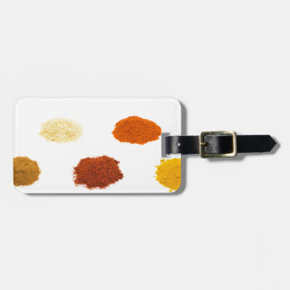 Heaps of several seasoning spices on white luggage tag
