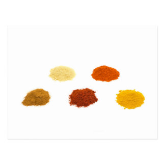 Heaps of several seasoning spices on white postcard