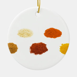 Heaps of several seasoning spices on white round ceramic ornament