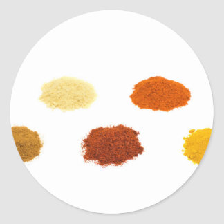 Heaps of several seasoning spices on white round sticker