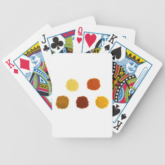 Heaps of various seasoning spices on white bicycle playing cards