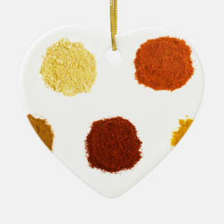 Heaps of various seasoning spices on white ceramic heart ornament