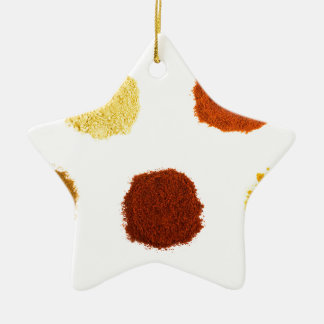 Heaps of various seasoning spices on white ceramic star ornament