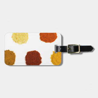 Heaps of various seasoning spices on white luggage tag