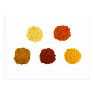 Heaps of various seasoning spices on white postcard