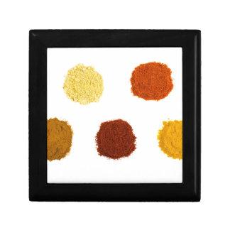 Heaps of various seasoning spices on white trinket box