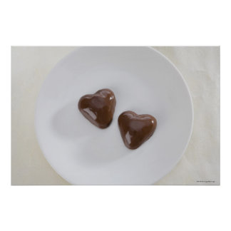 Heart shaped chocolate candies on a plate poster