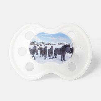 Herd of black frisian horses in winter snow baby pacifiers