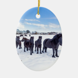 Herd of black frisian horses in winter snow ceramic oval ornament