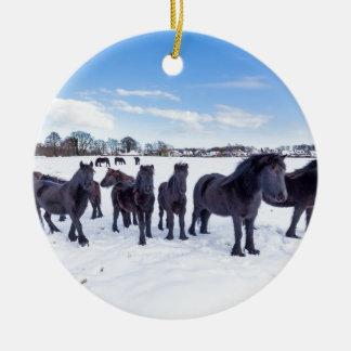 Herd of black frisian horses in winter snow round ceramic ornament
