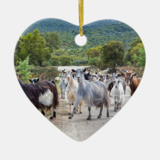 Herd of mountain goats walking on road ceramic heart ornament