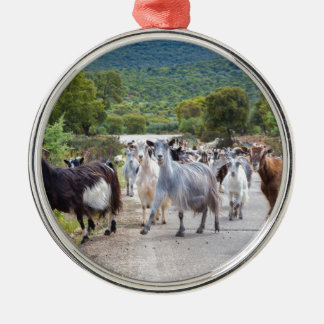 Herd of mountain goats walking on road Silver-Colored round ornament