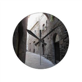 Hidden alley in Volterra village, province of Pisa Round Clock