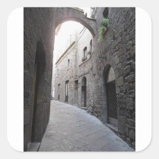 Hidden alley in Volterra village, province of Pisa Square Sticker
