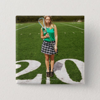 High school lacrosse player (16-18) holding 2 inch square button