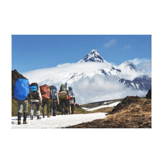 Hikers climbing on mount on background volcanoes canvas print