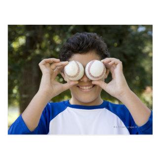 Hispanic teenage boy covering eyes with postcard