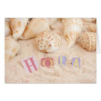 Hola, hello in Spanish on a sandy beach Card