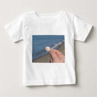 Holding a seashell in the hand baby T-Shirt