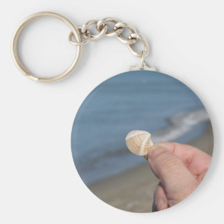 Holding a seashell in the hand basic round button keychain