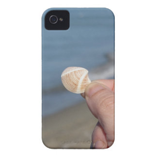 Holding a seashell in the hand iPhone 4 cases