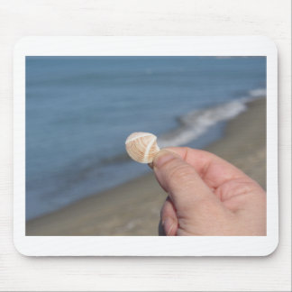 Holding a seashell in the hand mouse pad
