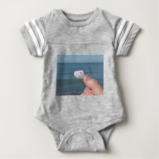 Holding a seashell in the hand with blue sea baby bodysuit