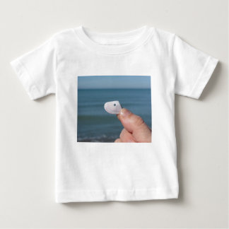 Holding a seashell in the hand with blue sea baby T-Shirt