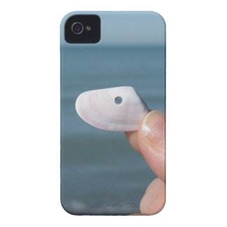 Holding a seashell in the hand with blue sea iPhone 4 Case-Mate case