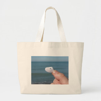 Holding a seashell in the hand with blue sea large tote bag