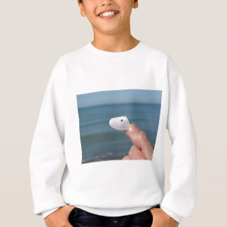 Holding a seashell in the hand with blue sea sweatshirt