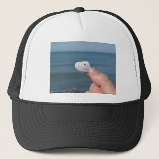 Holding a seashell in the hand with blue sea trucker hat