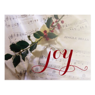 Holly branch on top of sheet music for Christmas Postcard