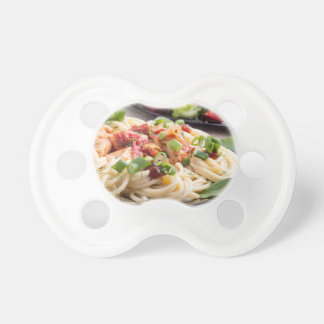Home-cooked meals on a gray mat - spaghetti pacifiers