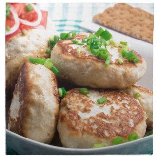 Homemade chicken burgers and tomato salad napkin