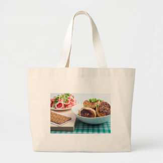 Homemade fried meatballs in a white bowl closeup large tote bag