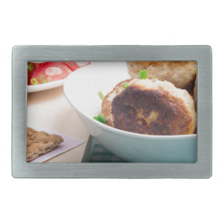 Homemade fried meatballs in a white bowl closeup rectangular belt buckles