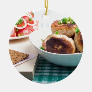 Homemade fried meatballs in a white bowl closeup round ceramic ornament