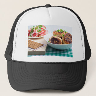 Homemade fried meatballs in a white bowl closeup trucker hat