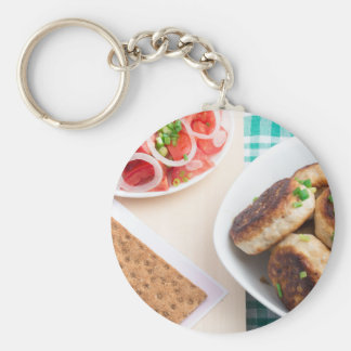 Homemade fried meatballs on a green tablecloth basic round button keychain