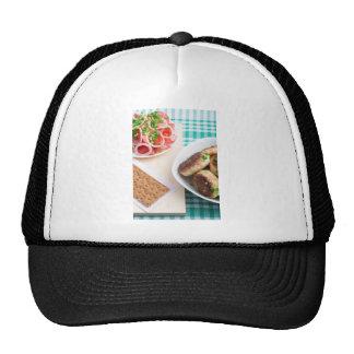 Homemade fried meatballs on a green tablecloth trucker hat