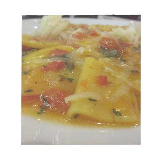 Homemade pasta with tomato sauce, onion, basil notepad