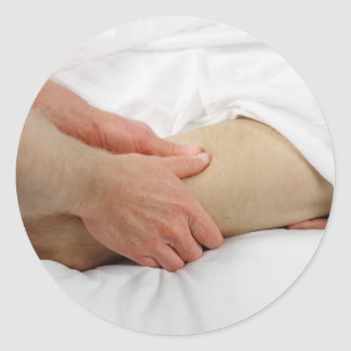 Homme ayant le massage de jambe sticker rond