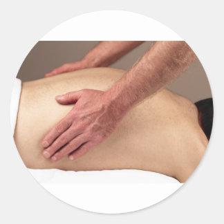 Homme massant les arrières d'un client de massage autocollants ronds