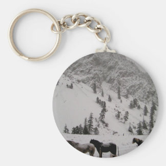Horses in the snow in the mountains basic round button keychain