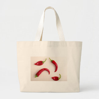Hot chili peppers on a light wooden board large tote bag